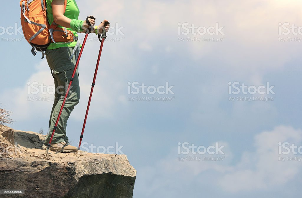 young woman hiker enjoy the view at mountain peak cliff stock photo