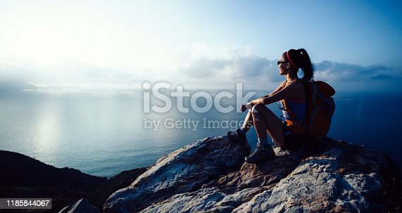 Young woman hiker enjoy the view at sunrise seaside mountain peak