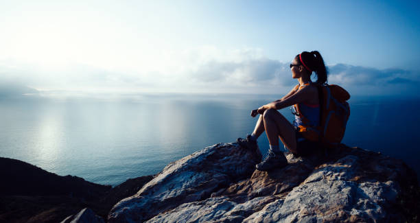 Young woman hiker enjoy the view at sunrise seaside mountain peak stock photo