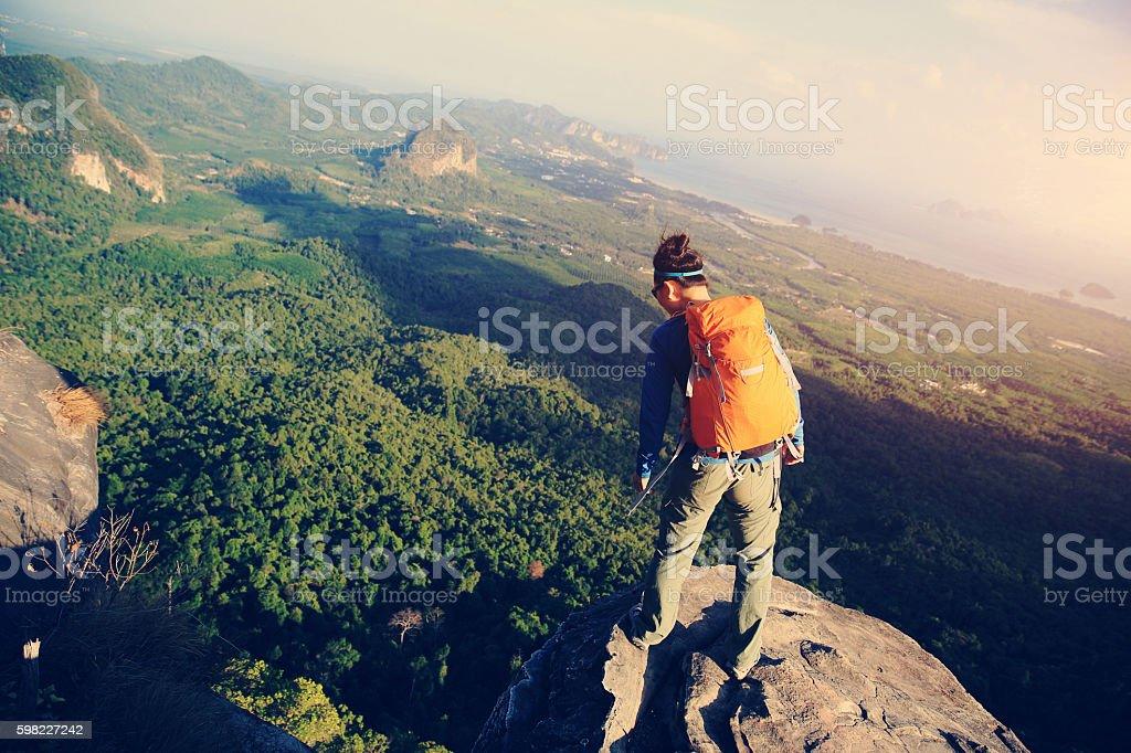 Jovem mulher alpinista no pico da montanha penhasco foto royalty-free