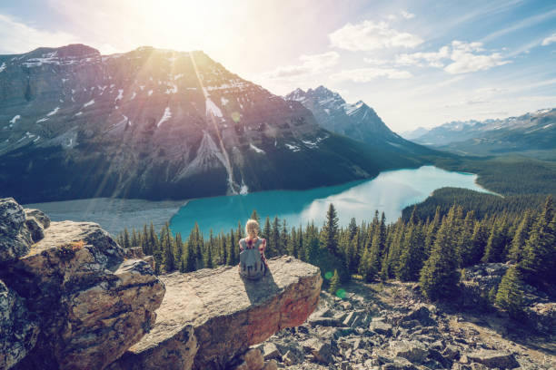 Young woman hiker on top of mountain Young woman hiker on rock above mountain lake in Springtime. People success in nature concept canadian rockies stock pictures, royalty-free photos & images