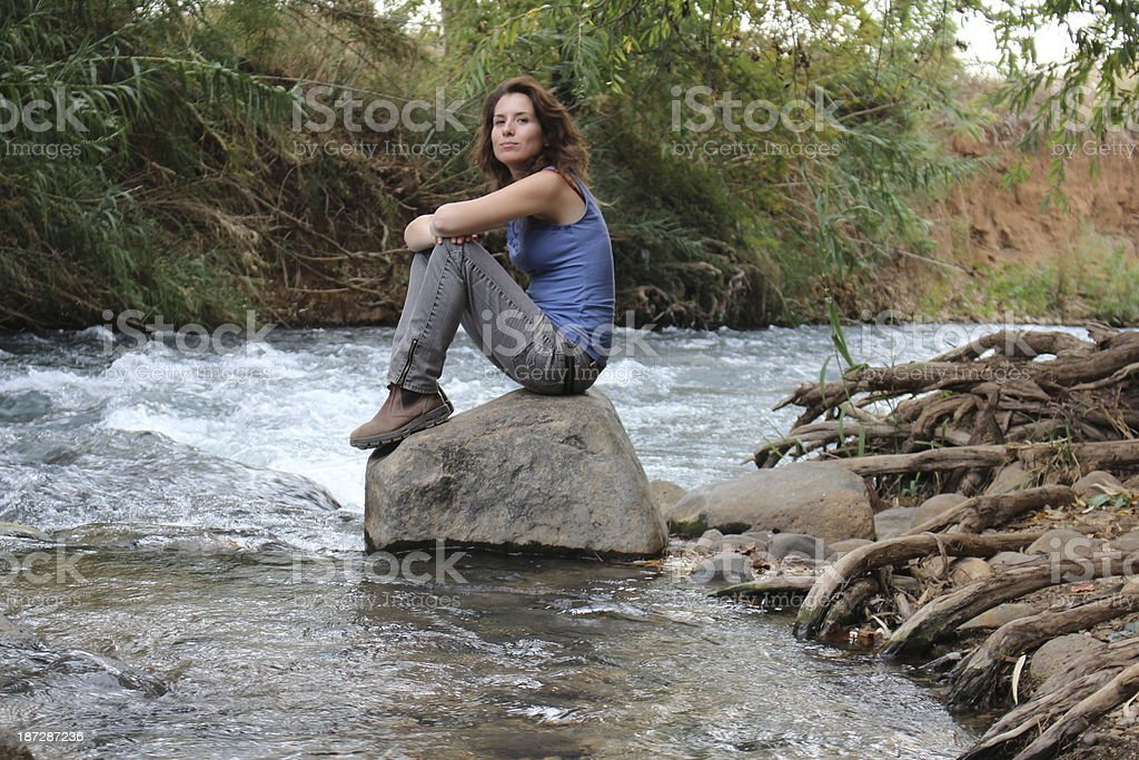 Young woman hiker resting at a stream stock photo