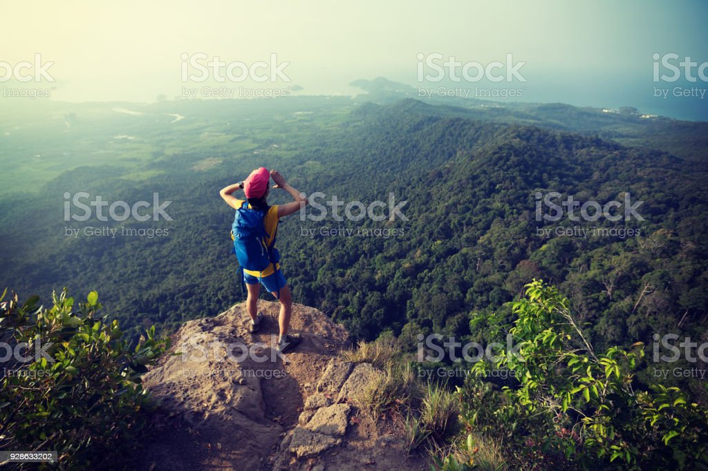 Young woman hiker shouting on mountain peak cliff edge – zdjęcie