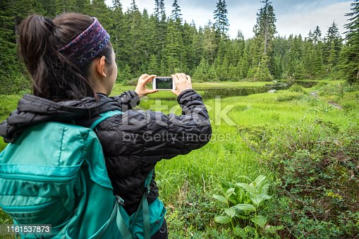 903015102istockphoto Young Woman Hiker Taking Photo of Alpine Lake with Smartphone 1161537873