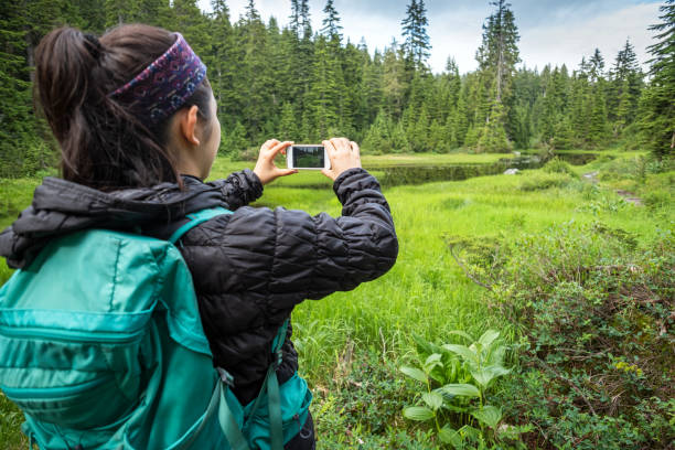Young Woman Hiker Taking Photo of Alpine Lake with Smartphone stock photo