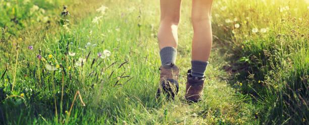 Junge Wanderin wandert auf Wanderweg im Grasland – Foto