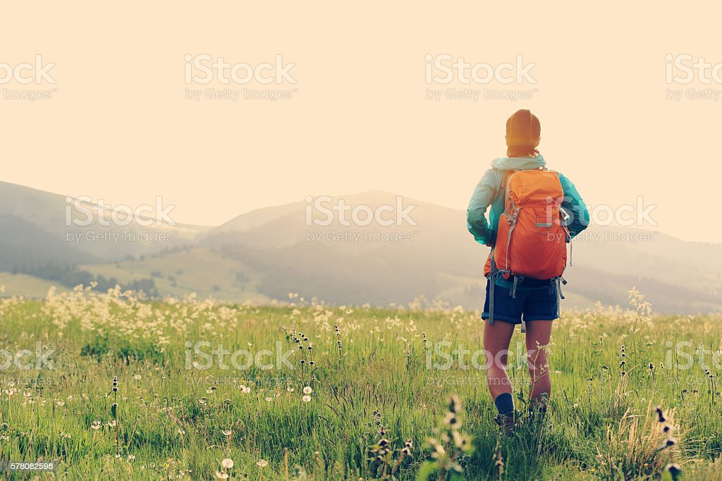 young woman hiker walking on trail in grassland – Foto