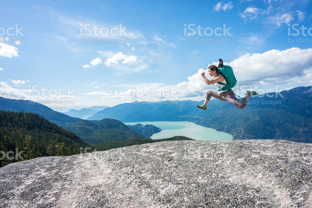 Young Woman Hiker with Backpack Jumping on Wilderness Mountaintop, Canada stok fotoğrafı