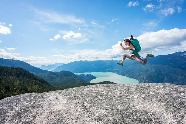 Young Woman Hiker with Backpack Jumping on Wilderness Mountaintop, Canada stock photo