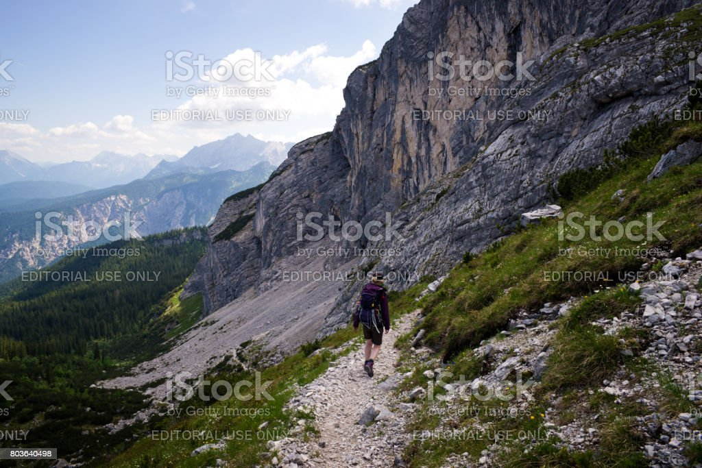 Young woman hikes through mountain landscape in bavarian alps stock photo