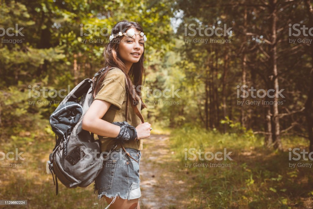 Young woman hiking in forest Portrait of young woman hiking in forest. Beautiful hipster is carrying backpack. Adventurous female is enjoying her summer vacation. Active Lifestyle Stock Photo
