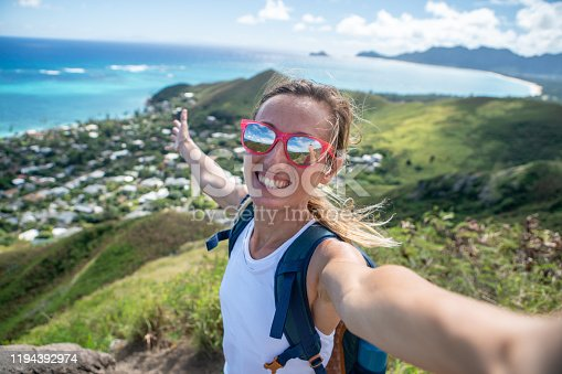 Young woman on mountain top overlooking the ocean taking selfie portrait using mobile phone, Oahu, Hawaii, USA