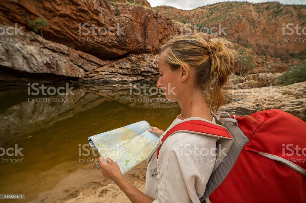 Caucasian female hiking in the Australia\'s outback reads a map for...