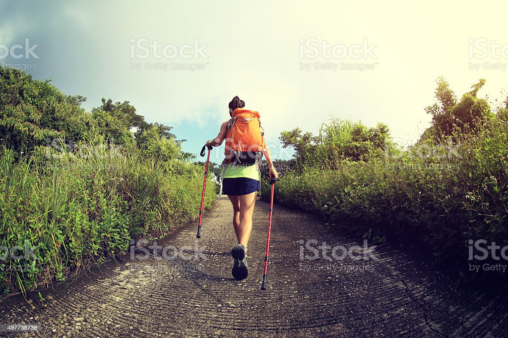 young   woman hiking on mountain trail stock photo