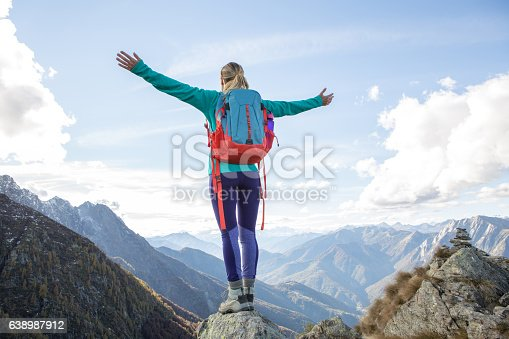 istock Young woman hiking reaches mountain top, outstretches arms 638987912