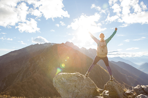 istock Young woman hiking reaches the mountain top, outstretches arms 637008970