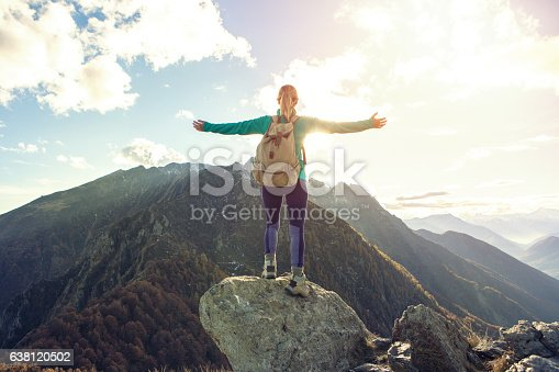 istock Young woman hiking reaches the mountain top, outstretches arms 638120502