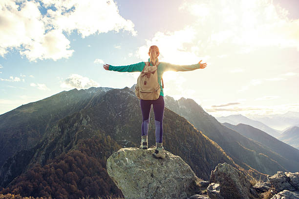 Young woman hiking reaches the mountain top, outstretches arms stock photo