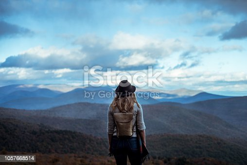 A photograph of a young woman hiking through the mountains in the fall or early winter enjoying the view.