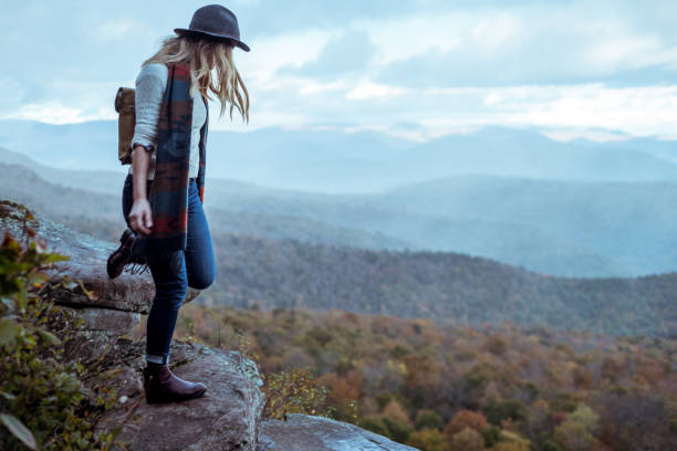 Young woman hiking through beautiful mountains. A photograph of a young woman hiking through the mountains in the fall or early winter enjoying the view. catskill mountains stock pictures, royalty-free photos & images