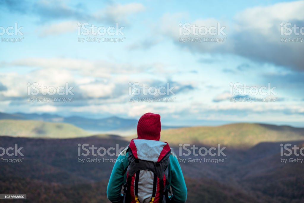 Young woman hiking through beautiful mountains. A photograph of a young woman hiking through the mountains in the fall or early winter enjoying the view. Adult Stock Photo