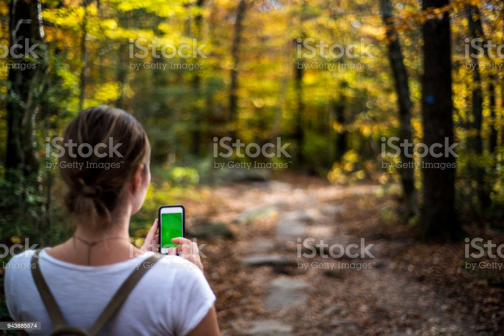 A young woman hiking with a cell phone stock photo