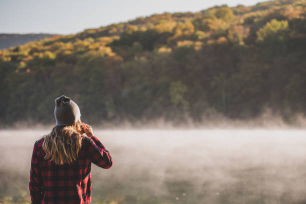 Young woman hiking with coffee stock photo