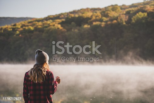 A young woman is hiking and walking with coffee while camping at a lake in the morning.