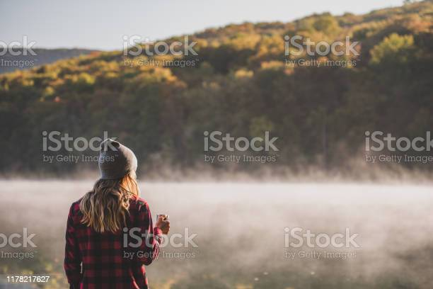 Photo of Young woman hiking with coffee