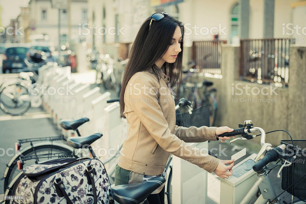 Young Woman Hiring A Public Bicycle stock photo