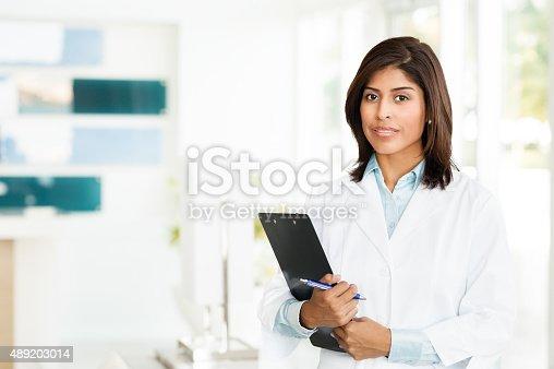 Twenty-something hispanic female doctor nurse taking notes in Office