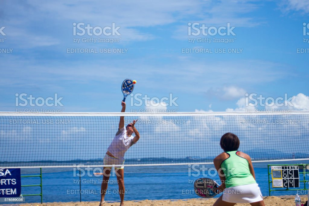Young woman hit a tennis ball on the beach - foto stock