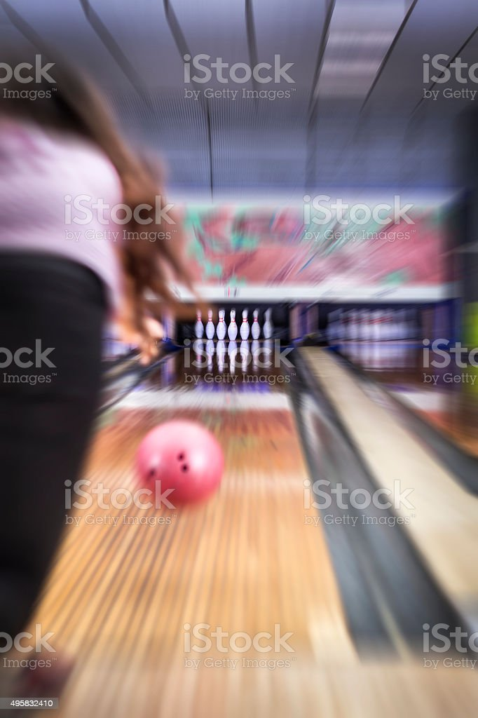 Young woman hitting a bowling ball - Blurred zoom effect - Focus on...