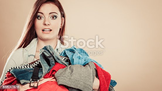 460589747 istock photo Young woman hold pile of clothes. 838047678