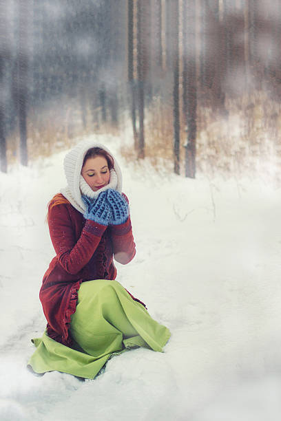 Young woman hold snow in mittens. Snowy forest Christmas background. stock photo