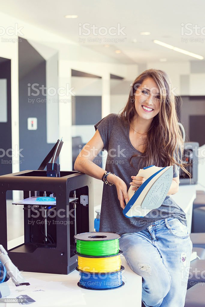 Young woman holding 3D printout - an iron Young woman sitting by the 3D printer and holding 3D printout - an iron, smiling at the camera. 2015 Stock Photo