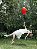 Young woman holding a balloon, floating