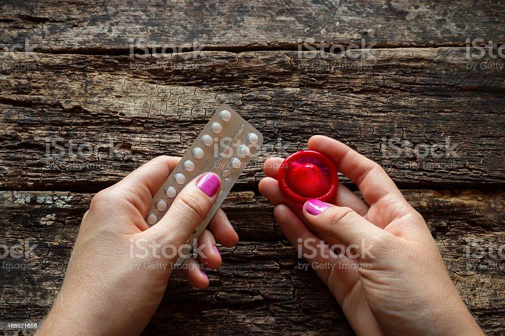 Junge Frau hält eine birth control-Details und ein Kondom – Foto