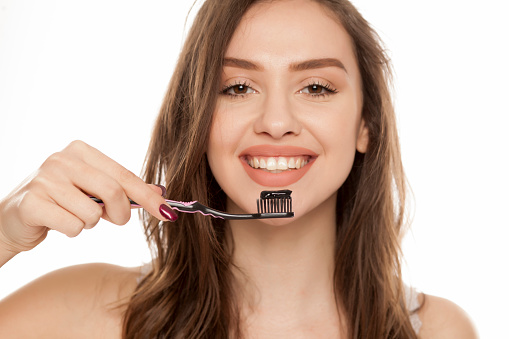 Young Woman Holding A Black Tooth Paste With Active Charcoal And Black Tooth Brush On White Background Stock Photo - Download Image Now