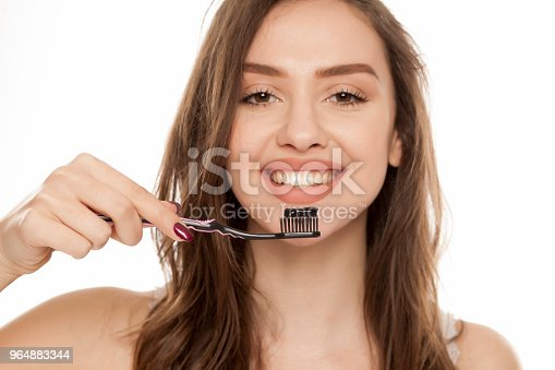 Young Woman Holding A Black Tooth Paste With Active Charcoal And Black Tooth Brush On White Background Stock Photo & More Pictures of Adult