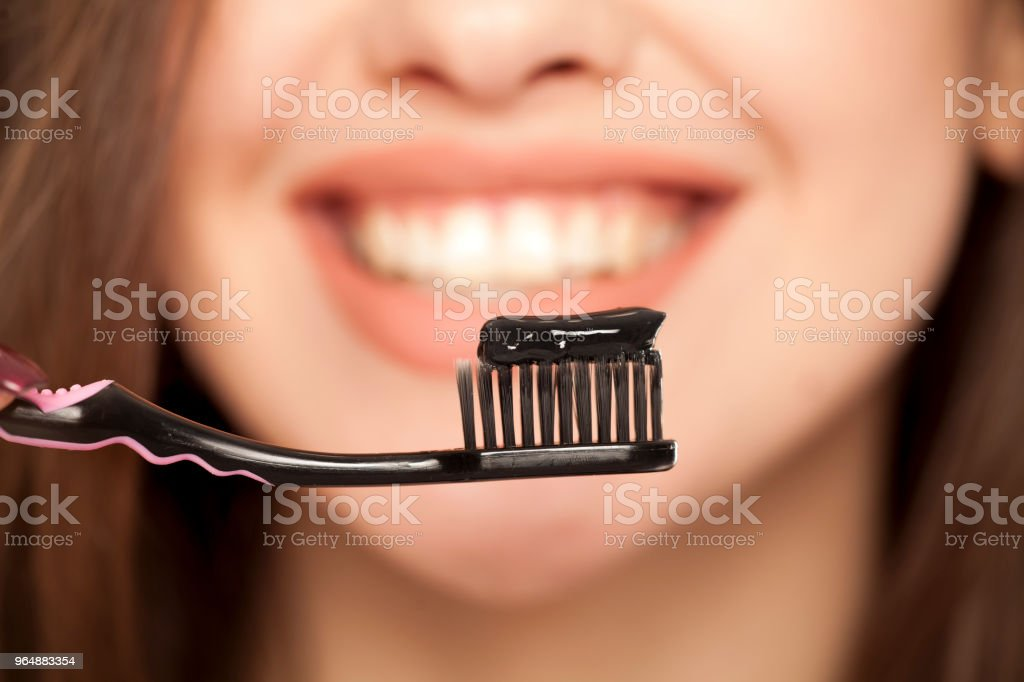young woman holding a black tooth paste with active charcoal, and black tooth brush on white background stock photo