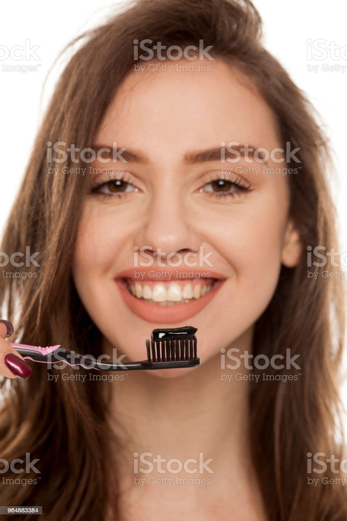young woman holding a black tooth paste with active charcoal, and black tooth brush on white background royalty-free stock photo