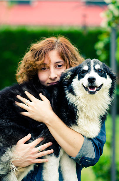 young woman holding a border collie dog in her arms foto