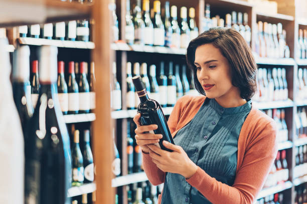 Young woman holding a bottle in the wine shop stock photo