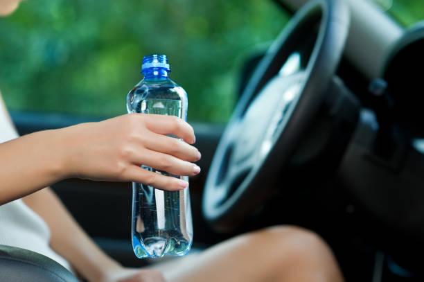 joven sosteniendo una botella de agua mientras está sentada al volante de cerca - foto de stock