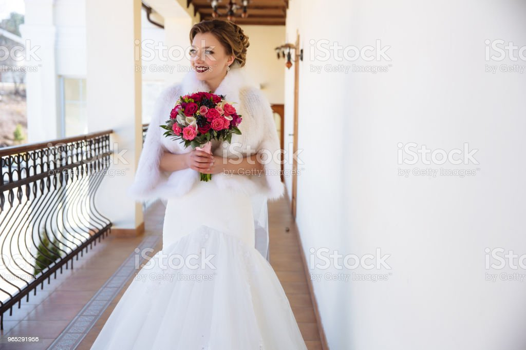 Young woman holding a bouquet of pink and red roses and looking into the distance, smiling broadly. A girl with bright lipstick laughs and rejoices at the wedding zbiór zdjęć royalty-free