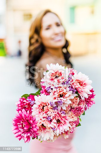 A young woman holding a bouquet of wildflowers in her hands .