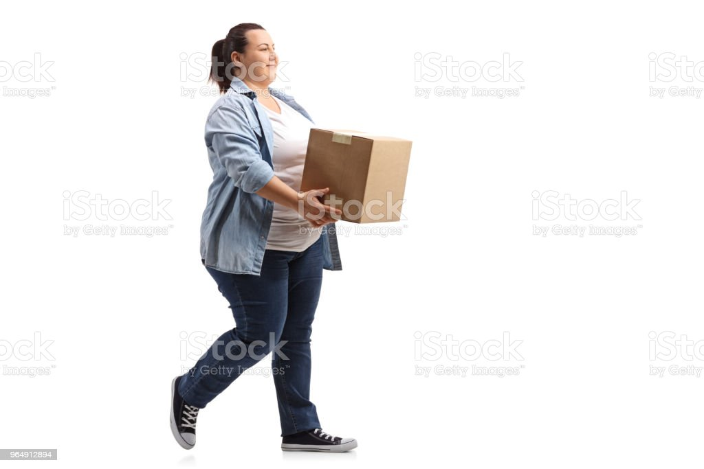 Young woman holding a box and walking royalty-free stock photo