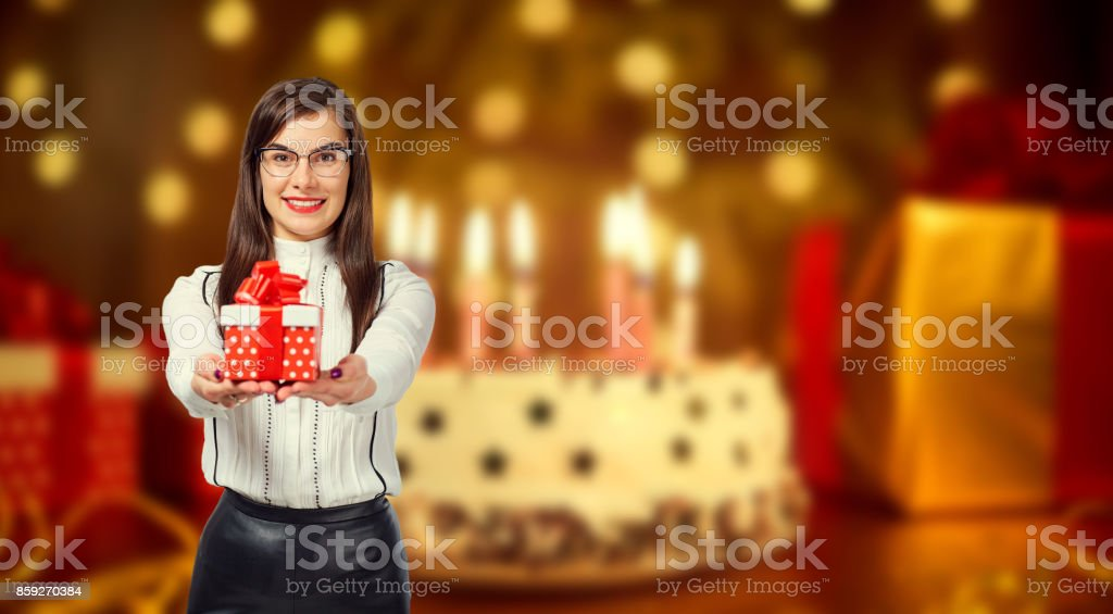 Young woman holding a box with a gift on the background of a bir stock photo