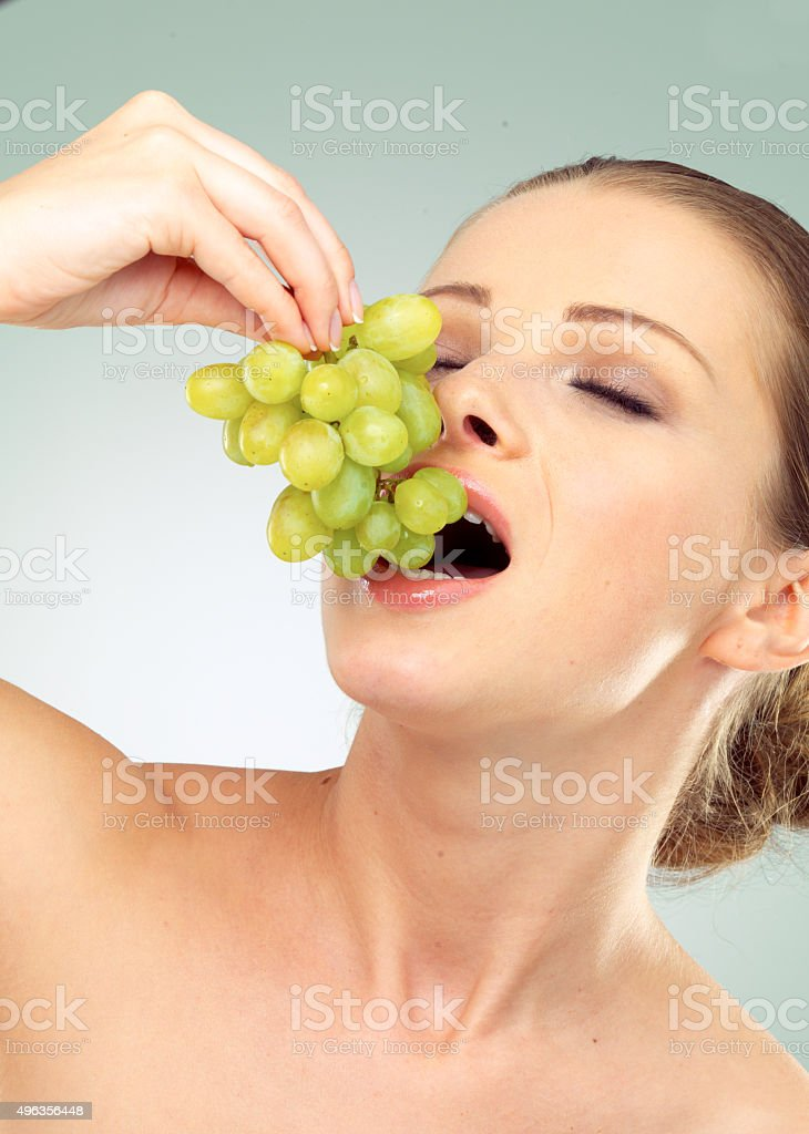 Young Woman Holding A Bunch Of Green Grapes Stock Photo